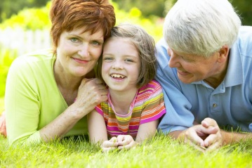 vibrant grandparents and young girl laying in grass